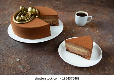 A large delicious chocolate cake and a piece of cake on a white plate with a cup of coffee on a beautiful background for the holiday