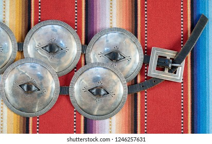 Large Diameter Concho, Navajo First Phase Style Silver Concha Belt. Sterling Silver with a leather belt with intricate craftsmanship, on a colorful woven textile background.