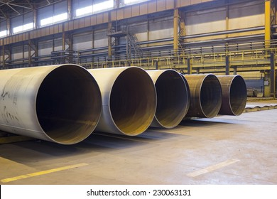 Large diameter pipes are stacked in an industrial factory shop