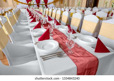 Large dining hall with tables set up white tablecloth
