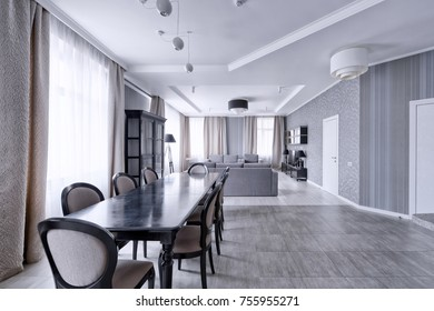 Large dining table in the interior of the apartment in a stylish modern design.