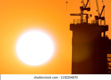 a large disc of the setting sun in the orange sky, a dark contrasting silhouette of a house under construction and building cranes