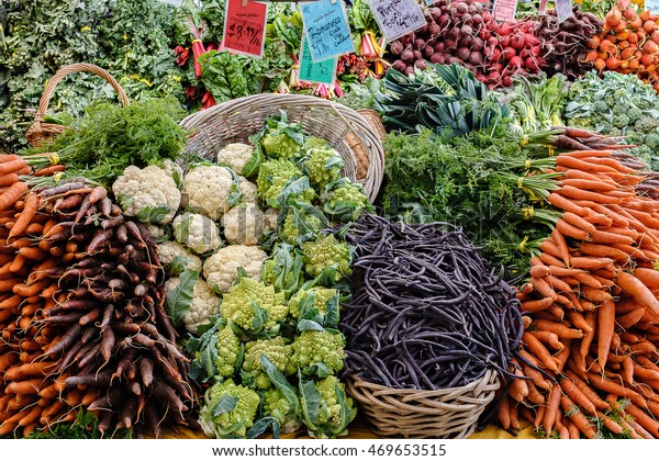 Large display of organic vegetables at an outdoor farmers market in Seattle.