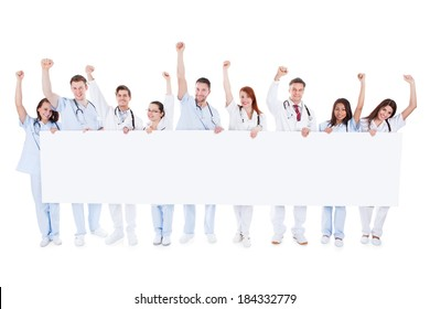 Large diverse group of healthcare personnel standing in a line holding a blank white banner with copyspace and cheering raising their fists in the air isolated on white