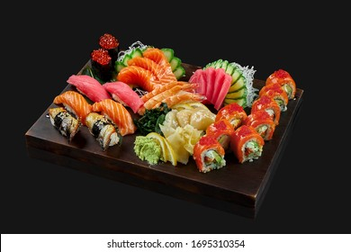 A large, diverse set with sushi, fresh sashimi and Philadelphia roll. Sushi with tuna, eel and salmon, shrimp, tuna, scallop and salmon sashimi and roll on a wooden tray. Photo for menu