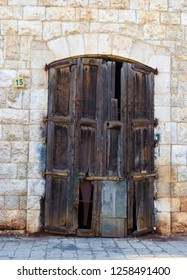 large  door with old used wooden clusters on the facade of an hold stone house, in Jounieh, Lebanon