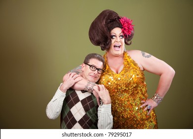 Large drag queen holds a surprised nerd around his neck