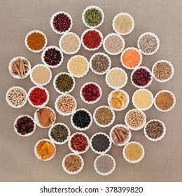 Large dried superfood selection in porcelain bowls in a circular design over hessian background.