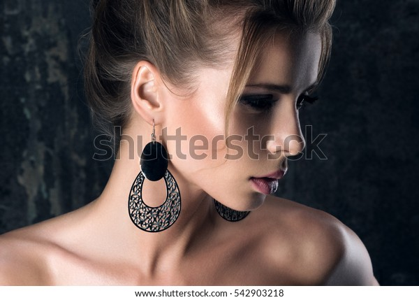 Large earrings. Closeup portrait in the shadows of a young woman in profile. Clean skin, make-up and hairstyle. The dark background
