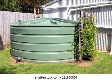 Large eco- friendly water storage tank in suburban backyard