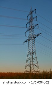 Large Electricity pylon also overhead line pylon stands in the wheat field, dark blue evening sky. Germany.