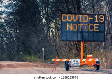 Large electronic notification sign on rural street announcing road closure due to Coronavirus Covid-19 pandemic