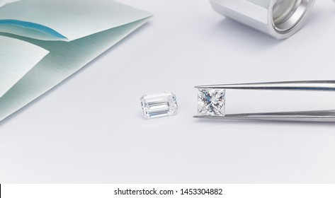 Large Emerald Cut and Princess Cut Diamonds in Tweezers with Magnifying Glass and Diamond Parcel Paper