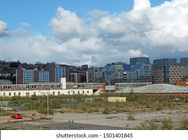 a large empty brownfield site in leeds england with weeds growing through concrete and a burned out abandoned car surrounded by city apartment buildings