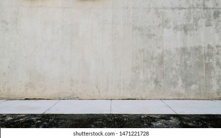 Large empty grunge wall and white sidewalk.