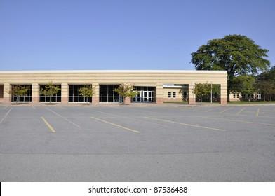 Large empty macadam parking area by an modern school building