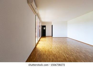Large empty room with white walls and 70's parquet. Nobody inside