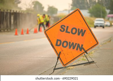 A large, English construction sign reminds motorists to slow down while road construction is underway.