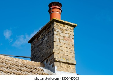 Large, english cottage style brick chimney showing a newly installed terracotta pot together with a chimney cover to prevent birds nesting. Part of the roofing can also be seen.