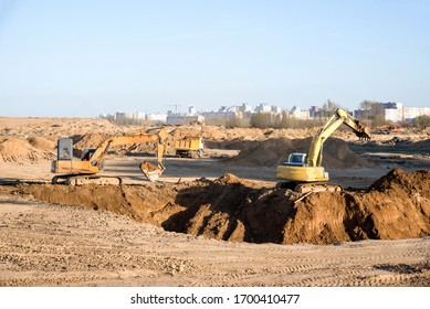 Large excavator working at construction site. Backhoe during earthworks on sand open-pit. Digging ground for the foundation and for laying sewer pipes district heating. Earth-moving heavy equipment