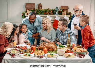 large family celebrating christmas and looking at little girl together