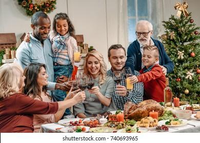 large family clinking glasses on christmas dinner