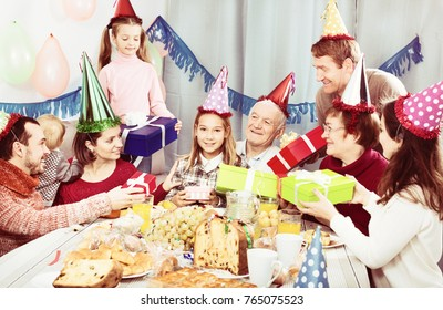 Large family handing gifts to birthday girl during dinner