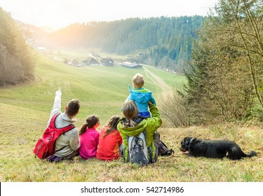 Large family having trekking vacation day in switzerland mountains - Father, mother, two children daughters,one son and dog pet having fun in nature - Love concept - Focus on people - Warm filter