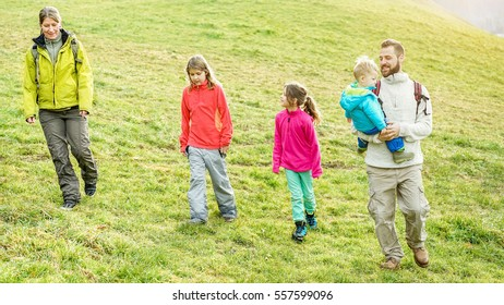 Large family having trekking walking day in landscape mountains during summer time - People having fun camping in holidays - Health ad vacation concept  - Warm filter
