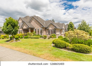 Large family house in the suburbs of Canada with beautiful front yard in the summer.