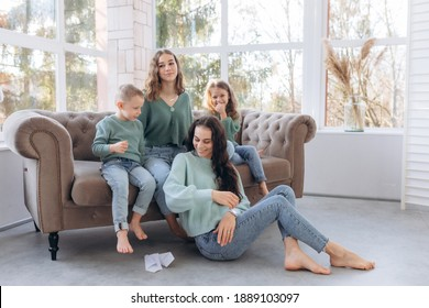 Large family. A mother of many children. Kids hugging mom while sitting on sofa. The guy launches a paper airplane All dressed in the same sweaters