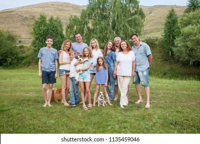 Large family outdoors. Mother, father, children, grandmother, grandfather and dog