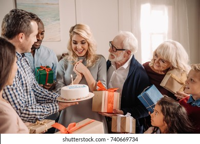 large family presenting cake and gifts to happy surprised woman