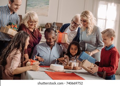 large family presenting cake and gifts to happy african american man