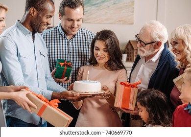 large family presenting cake and gifts to beautiful surprised woman