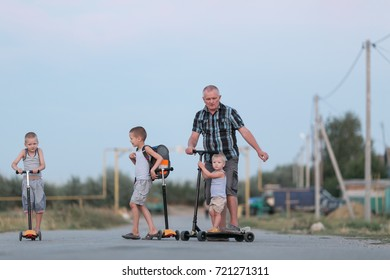 A large family is riding a scooter along a village street. The concept of a sports family.