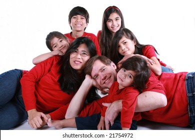 Large family of seven in red shirts and jeans isolated on white