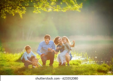 A large family is walking his beagle in a park by the lake. Mom enjoys the hair of her daughter, and her father and son train the dog