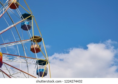A large Ferris wheel at an amusement Park on a background of blue sky. Several cabins with roofs in the form of umbrellas. The sturdy construction is decorated with colorful bulbs.