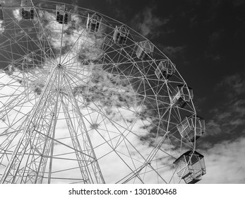 A large Ferris Wheel with a moody sky behind it. Shot in black and white