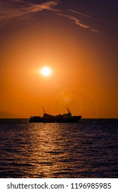 Large ferry boat at sunset on the Aegean Sea leaving Samothrace Island in Greece at sunset with lens flare in the shot