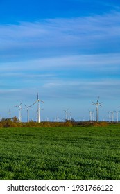a large field and wind turbines, in summer with a blue sky