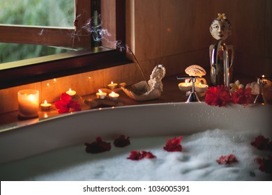 Large Filled Bath with Foam and Flowers. Romantic Atmosphere, Burning Scented Candles and Aromasticks