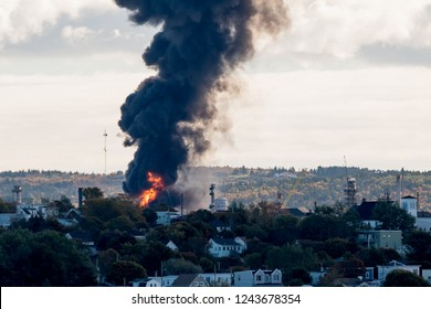 Large fire at an oil refinery seen from a distance. Only parts of the refinery visible behind the trees. Thick black smoke rises from the flames.