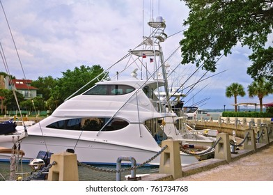 Large fishing boat docked at a marina on the ocean with condominiums in the background.