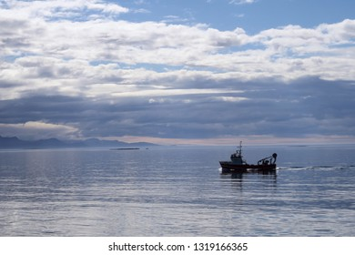 Large fishing boat on calm sea with overcoast clouds, off the coast of the West Fjords of Iceland