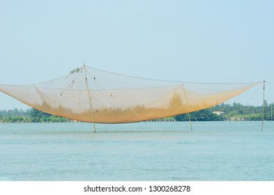 A large fishing net stretched between bamboo poles. The sky is blue and clear. A stretch of land covered with trees and houses is in the background.