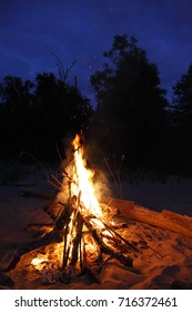 A large flaming bonfire in the sand in the evening.