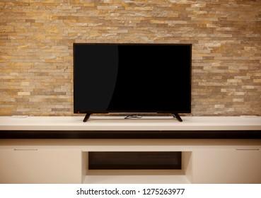 large flat screen TV on a white shelf, stone wall
