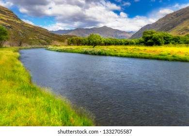 Large flowing stream leading up to mountains in background. New Zealand landscape background. Exploring NZ wilderness hiking outdoors.